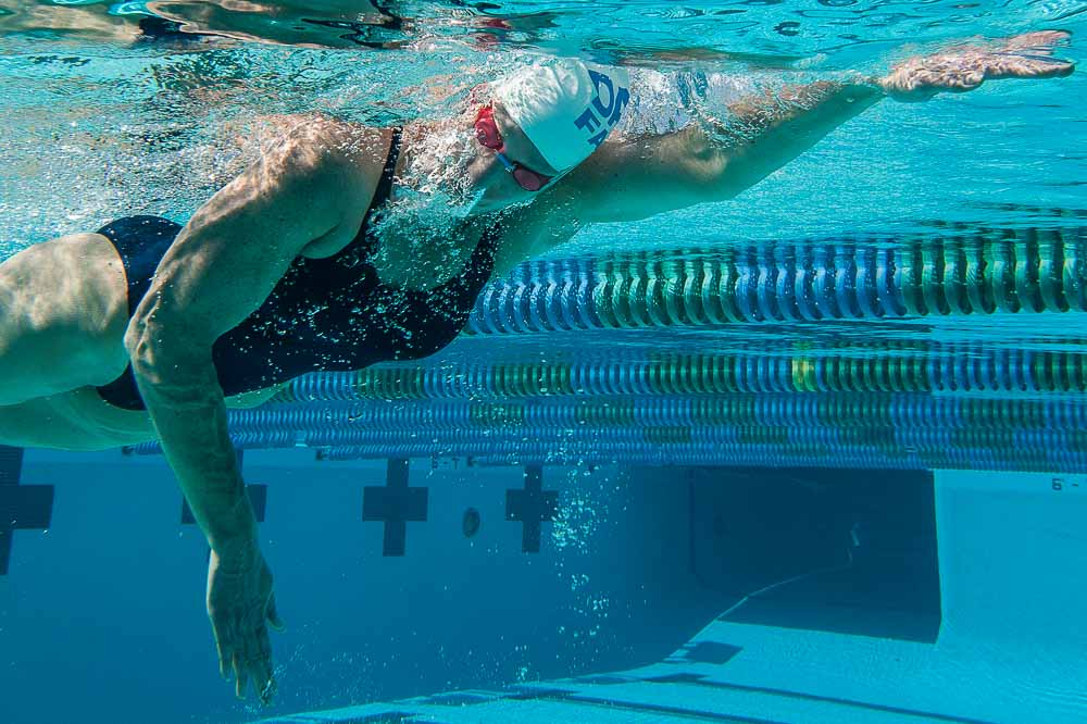 Female swimmer in black bathing suit, red goggles, white cap, blowing bubbles underwater while doing freestyle