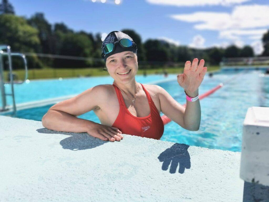 Oxana waving in outdoor pool